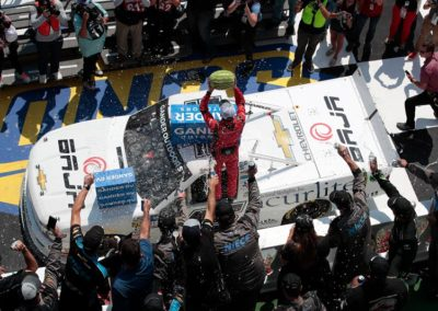 Ross Chastain holds a watermelon aloft in victory lane after taking the checkered flag in his Acurlite sponsored race truck at the conclusion of the NASCAR Gander Outdoors Truck Series race at Pocono Raceway.